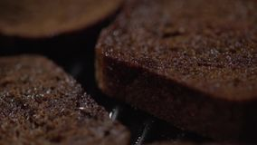 Um close-up de uma parte de pão que cai em uma frigideira com nervuras vídeos de arquivo