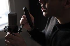 Um close-up dos bordos no microfone de uma posição do homem novo do canto Imagens de Stock Royalty Free