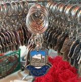 Um close up em um suporte chave azul de prata na forma da talismã árabe de Hamsa com o Jerusalém da palavra impressa nele foto de stock