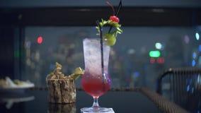 Um cocktail alaranjado colorido com gelo na tabela no skybar, negligenciando os arranha-c?us da noite Borr?o do fundo 4K vídeos de arquivo