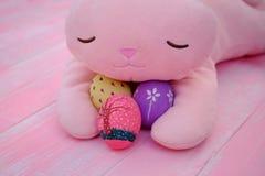 Um coelho enchido cor-de-rosa que abraça ovos da páscoa pintados à mão no assoalho de madeira da aflição pastel cor-de-rosa foto de stock