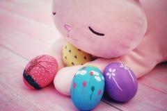 Um coelho enchido cor-de-rosa que abraça ovos da páscoa pintados à mão no assoalho de madeira da aflição pastel cor-de-rosa imagem de stock
