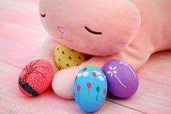 Um coelho enchido cor-de-rosa que abraça ovos da páscoa pintados à mão no assoalho de madeira da aflição pastel cor-de-rosa fotos de stock royalty free