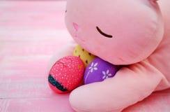 Um coelho enchido cor-de-rosa que abraça ovos da páscoa pintados à mão no assoalho de madeira da aflição pastel cor-de-rosa imagem de stock royalty free