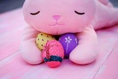 Um coelho enchido cor-de-rosa que abraça ovos da páscoa pintados à mão no assoalho de madeira da aflição pastel cor-de-rosa fotografia de stock royalty free