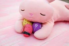 Um coelho enchido cor-de-rosa que abraça ovos da páscoa pintados à mão no assoalho de madeira da aflição pastel cor-de-rosa imagens de stock royalty free