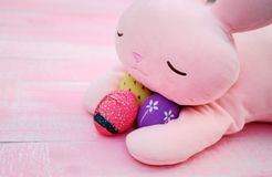 Um coelho enchido cor-de-rosa que abraça ovos da páscoa pintados à mão no assoalho de madeira da aflição pastel cor-de-rosa imagens de stock