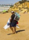 Um comerciante da praia que leva seu estoque de telas coloridas ao longo da praia em Albuferia em Portugal em um dia quente Fotografia de Stock