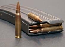 Um compartimento do rifle carregado com 223 balas em um fundo cinzento imagem de stock royalty free