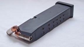 Um compartimento preto da pistola com uma bala de reposição ao lado dela Fotografia de Stock