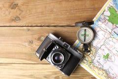 Um compasso da orientação, uma câmera velha e um resto geográfico do mapa em uma tabela de madeira com espaço da cópia para seu t fotografia de stock