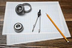 Um compasso de calibre vernier que guarda um rolamento, um lápis e um par de compassos que encontram-se sobre o projeto no fundo  fotografia de stock