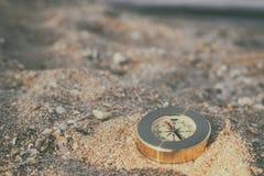 Um compasso que mostra o sentido encontra-se na areia do mar com shell imagens de stock