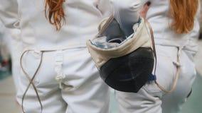 Um competiam grande no sal?o com muitos povos Adolescente na roupa protetora branca que guarda uma máscara protetora filme