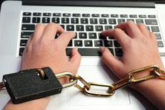 Um computador é amarrado a uma mão do ` s do homem por uma corrente resistente imagem de stock
