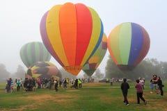 Um conjunto de balões de ar quente em um campo em um dia enevoado fotos de stock royalty free