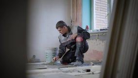 Um construtor adulto aplica com cuidado a mistura do cimento ao assoalho concreto e alinha a superfície com uma espátula filme