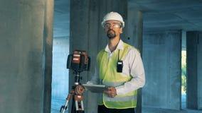 Um construtor, arquiteto trabalha com nível do laser em um canteiro de obras vídeos de arquivo