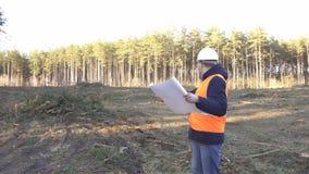 Um construtor masculino caucasiano examina um plano da construção e do desflorestamento para um local para a construção de um nov filme