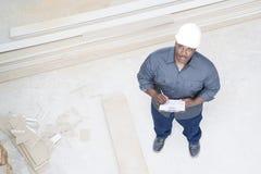 Um construtor que inspeciona uma casa imagem de stock royalty free