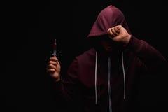 Um consumidor de droga em uma camiseta roxa com uma capa em sua cabeça sofre da toxicodependência em um fundo do preto escuro Foto de Stock Royalty Free