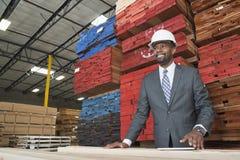 Um contratante masculino afro-americano que está na frente das pranchas de madeira empilhadas foto de stock