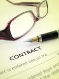 Um contrato com uma pena e vidros Imagens de Stock Royalty Free