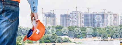 Um coordenador com um capacete de construção em sua mão está estando oposto ao grupo de arranha-céus da cidade O conceito é o des imagens de stock royalty free