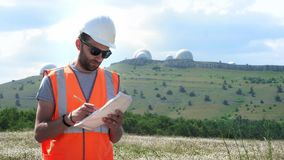 Um coordenador masculino em um capacete e em uma veste brancos completa documentos, guarda folhas de papel em suas mãos Contra o  filme