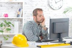 Um coordenador novo pensativo em seu computador imagem de stock