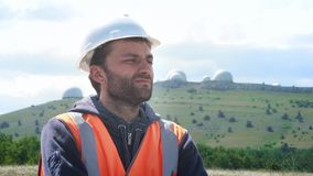 Um coordenador ou um construtor em um capacete branco e uma veste masculinos, suportes contra o contexto de diversos hemisférios  video estoque