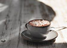 Um copo antigo do latte do leite com marshmallows em um fundo de madeira cinzento Uma bebida doce em um copo da porcelana imagem de stock