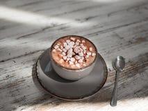 Um copo bonito do café do leite com marshmallows em um fundo de madeira cinzento Uma bebida do cacau em um copo da porcelana foto de stock