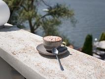 Um copo bonito do chocolate quente com marshmallows em um fundo borrado do mar Uma bebida do cacau em um copo da porcelana fotografia de stock royalty free