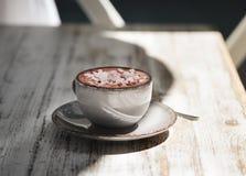 Um copo bonito do latte do leite com marshmallows e canela em um fundo de madeira da tabela Uma bebida do cacau em uma porcelana imagem de stock