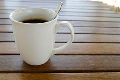 Um copo cerâmico branco com uma manhã que refresca o café quente com bebida do chá e a colher de chá brilhante do chá está em uma foto de stock
