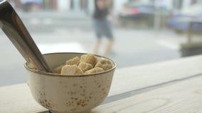 Um copo com tenazes de brasa do açúcar está na tabela no café Contém o açúcar mascavado Close-up video estoque