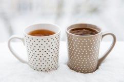 Um copo da bebida quente no fundo fresco da neve Fotos de Stock