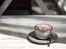 Um copo da porcelana do café preto com marshmallows brancos em um fundo de madeira gasto Uma bebida do cacau em uma caneca da arg foto de stock royalty free