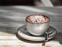 Um copo da porcelana do café preto com marshmallows brancos em um fundo de madeira gasto Uma bebida do cacau em uma caneca da arg imagem de stock