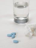 Um copo de água & de tabuletas azuis Imagem de Stock Royalty Free