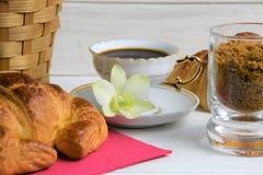 Um copo de café com café quente em uns pires, croissant, cesta do artigo, flor, açúcar mascavado em um fundo pintado de madeira fotos de stock royalty free