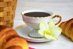 Um copo de café com café quente em uns pires, croissant, cesta do artigo, flor em um fundo pintado de madeira imagens de stock royalty free