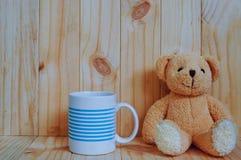 Um copo de café com urso de peluche e fundo de madeira Fotos de Stock