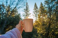 Um copo de café sustentado a um nascer do sol Imagem de Stock