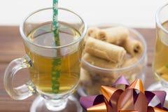 Um copo de chá com uma palha, uma bacia de cookies e uma curva brilhante Foto de Stock