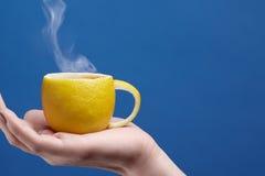 Um copo de chá feito do limão Copo do limão à disposição em um fundo azul Composição criativa no tema do chá natural do fruto Fotografia de Stock