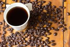 Um copo de papel do café preto e dos feijões de café na tabela Fotografia de Stock Royalty Free