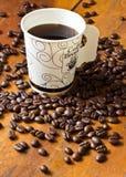 Um copo de papel do café preto e dos feijões de café na tabela Fotos de Stock Royalty Free