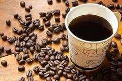 Um copo de papel do café preto e dos feijões de café na tabela Foto de Stock Royalty Free